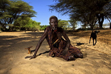 An elderly Turkana man rests in a dry river bed near the village of Kache Imeri. By his right hand is a small wooden head pillow. Northern Kenya is in the midst of a severe drought, and in the absence...