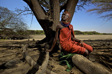 A young Turkana woman, wearing a bright red dress and many brightly coloured bead necklaces, seated on a tree root near Kataboi. Her head is coloured with red ochre. Northern Kenya is in the midst of...
