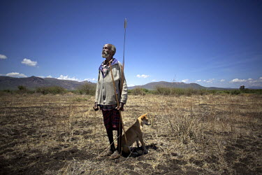 Peter Eshwaar who is 68 years old and from the Turkana community, stands ina  field which has not produced since 1997 due to lack of water.