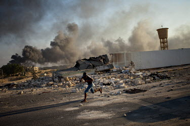 A man runs along a street near Gaddafi's recently taken residence in Tripoli. After a six month revolution, rebel forces finally managed to enter Tripoli and have taken control of Bab al-Aziziyah, Col...