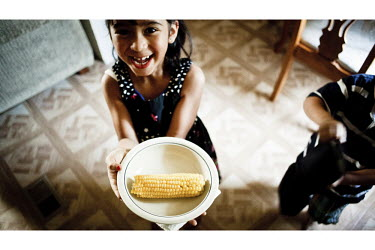 Wendy, the daughter of Mexican immigrants, with cooked corn in her trailer home, in Garden City, Kansas. This is home to many migrant workers who have come to the town to work at the Tyson meat packin...