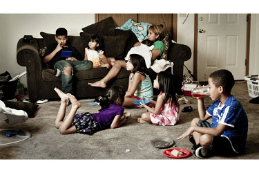 A Mexican family watching television at their home in Garden City, Kansas. They work at the nearby Tyson meat packing plant. Kansas dominates the American beef industry, producing 25% of all beef rais...