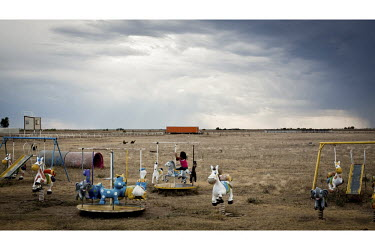 A child rides on a mini merry-go-round in a playground in Dodge City, Kansas. The area is home to many migrant workers who have come to the town to work in its meat packing plants. Kansas dominates th...