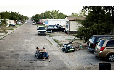 Children play with a toy car in a trailer park in Garden City, Kansas. This is home to many of the migrant workers who have come to the town to work at the Tyson meatpacking plant. The Tyson facility...