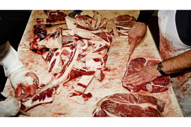 Staff butcher a beef carcass at a small family owned slaughter and meat packing company in Mead, Kansas. At this firm they typically slaughter ten animals each day but is one of only a few such sized...