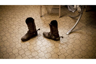A paired of spurred cowboy boots sit on an office floor in a feedyard in Mead, Kansas. A feedyard is part of the factory farming process where animals are fattened up prior to slaughter. They are most...