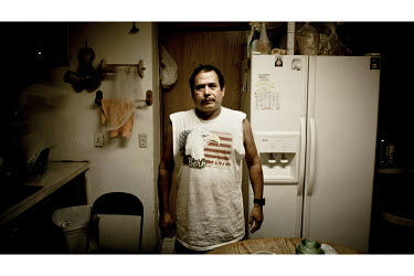A Mexican migrant stands in his kitchen in Garden City, Kansas. He is one of the many people who have come to the town to work at the Tyson meat packing plant. This facility kills and processes betwee...