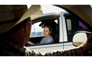 Todd Gorman talks to his daughter when their paths cross while driving their cars in and out of the feedeyard that he owns in Mead, Kansas. A feedyard is part of the factory farming process where anim...