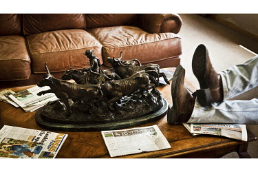 A man puts his feet up at an auction house in Dodge City, Kansas. The centrepiece of the table he rests on is a bronze statue of a cowboy herding beef cattle. Around the ornament are scattered various...