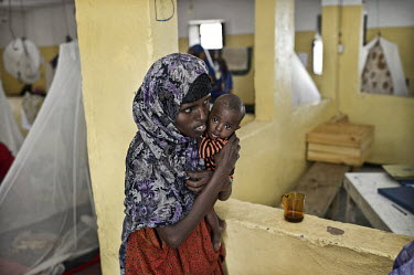A woman with her child in the TFC (Therapeutic Feeding Centre) ward of Galcayo hospital. Galcayo is a town in the self-declared autonomous state of Puntland. The populace in the region suffers from a...