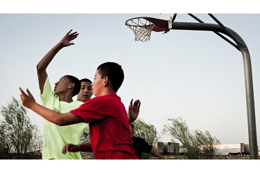 Children of migrant workers, who have come to Garden City to work at the Tyson meat packing plant, play basketball in a park where they live. The Tyson facility kills and processes between five and si...