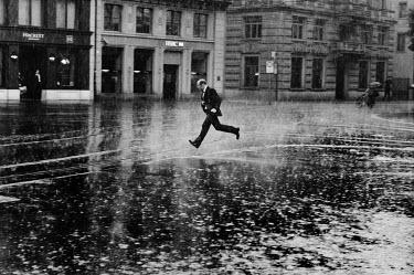 A man running through heavy rain across Paradeplatz, the symbolic centre of the Swiss banking industry in central Zurich. The Swiss banking industry holds an estimated 6,352 billion Swiss Francs (USD...