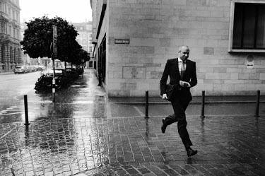 A banker caught in a sudden downpour runs past the headquarters of UBS, Switzerland's largest bank. The Swiss banking industry holds an estimated 6,352 billion Swiss Francs (USD 7,000 billion) in asse...