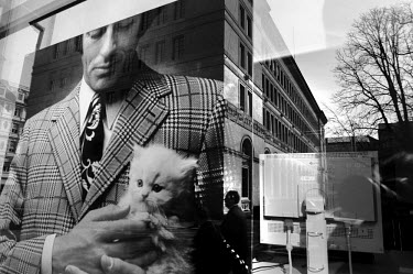 An exhibition photograph of a man holding a kitten at the Swiss National Bank archive. The building reflected in the background is the headquarters of the Swiss National Bank.