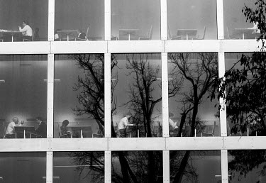 Employees in the Credit Suisse cafeteria building, with trees reflected in the windows. The Swiss banking industry holds an estimated 6,352 billion Swiss Francs (USD 7,000 billion) in assets, more tha...