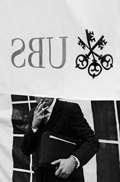A man smokes a cigarette during a break outside the annual general meeting of UBS, Switzerland's largest bank, during which there was a shareholder revolt over the bank's catastrophic losses. These we...
