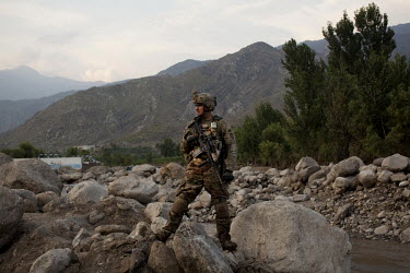 A US Army soldier from Gundog Company, 2-35 Infantry Regiment stands astride some riverside boulders while on patrol in the village of Watapur in the Pech Valley.
