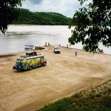 A colourfully painted bus at a landing stage on the Parana River.
