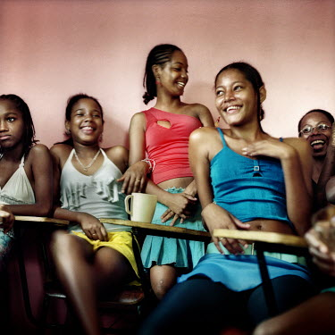 A group of young girls laugh with each other at a social centre in Candeal.