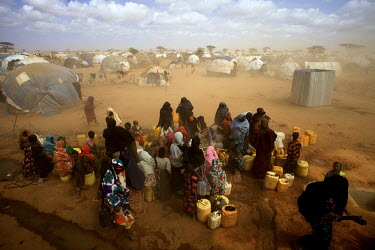 Women and children gather at a water point in the Dadaab refugee camp. Some 1,300 refugees fleeing East Africa's worst drought for 60 years are arriving at Dadaab each day. There are almost 400,000 di...
