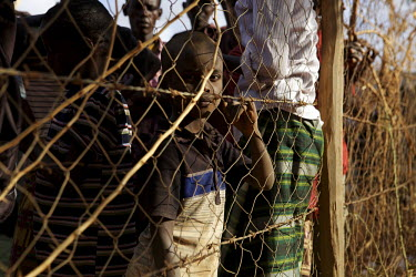 A Somali boy refugee looks through a wire fence while waiting at a reception point in the Dadaab refugee camp. Some 1,300 refugees fleeing East Africa's worst drought for 60 years are arriving at Dada...