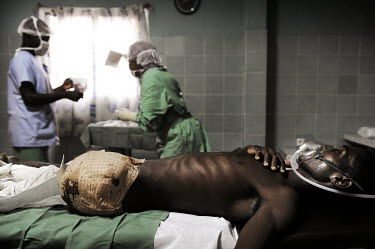 A man who lost his leg during fighting between forces of ousted former president Laurent Gbagbo and the current president Alassane Ouattara is treated in an operating theatre in the Nanan Yamusso Hosp...