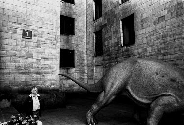 A man looks at a dinosaur statue at the Palace of Culture and Science in Warsaw.