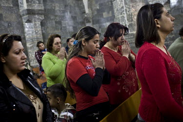 Christians during a morning service at Der Al Sayda monastery. They are among a number of people who have fled the city of Mosul, following increasing violence against Christians, and have found sanct...