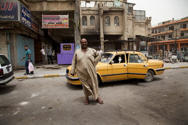 A man poses in front of a taxi at the intersection of Mutanabi and Al Rasheed streets in central Baghdad near the booksellers market.