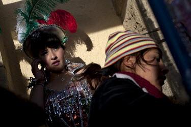 A woman prepares to dance at the Carnaval de Oruro. During the fiesta many people sacrifice llamas and give offerings such as coca leaves and cigarettes to show their dedication to the Devil, a Virgin...