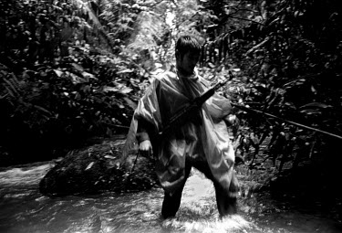 A Laotian ranger carrying a gun wades through a river on poaching patrol in the Bokeo Nature Reserve. The Bokeo Nature Reserve has a rich biodiversity of birds, insects and mammals including black gib...