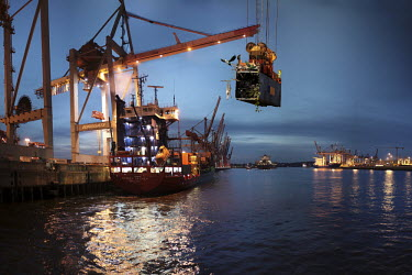 A composite, manipulated image showing the impact of climate change in an imagined future. Here, a shipping container, being tranferrred in Hamburg's harbour, has burst open to reveal a cargo of tropi...
