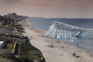 A composite manipulated image showing the impact of climate change in an imagined future. Here, an iceberg is washed ashore on a Spanish beach resort.