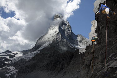 A composite, manipulated image showing the impact of climate change in an imagined future. Here, abseiling workers paint the Matterhorn white to replicate melted snow.