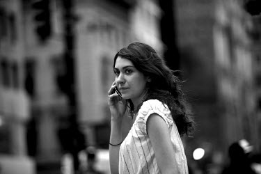 A young woman talks on her mobile phone while walking through Manhattan, New York
