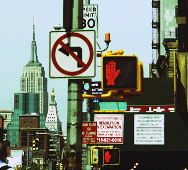Street signs, and the Empire State Building, seen from Manhattan's Lower East Side, New York.