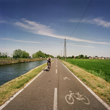 A cyclist rides down a path which runs alongside a 'naviglio' (canal) which runs from the centre of Milan to outlying villages including Cassinetta di Lugagnano. Cassinetta di Lugagnano is a 'model to...