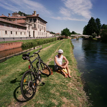 A cyclist sits resting on the side of a 'naviglio' (canal) which runs from the centre of Milan to outlying villages including Cassinetta di Lugagnano. Cassinetta di Lugagnano is a 'model town' in Lomb...