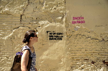 "A woman passes graffiti reading ""Not a Euro more for the banks"" as the Eurozone financial crisis continues to rage in Spain."