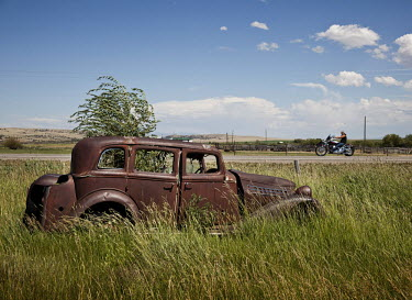 A biker rides past the rusting remnants of a vintage car lying in a field in Harrison, Montana.