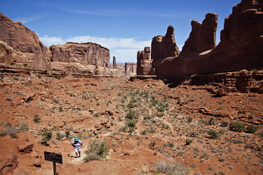 An overweight tourist struggles up a trail in Arches National Park, Utah.