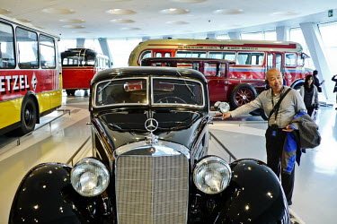 A visitor is photographed next to a classic Mercedes in the Mercedes-Benz museum in Stuttgart.