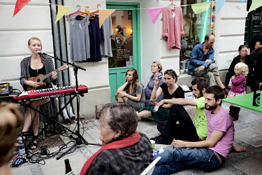 A crowd sit around a woman as she singings and plays a Ukelele on Jaeggersborggade in the Norrebro District.