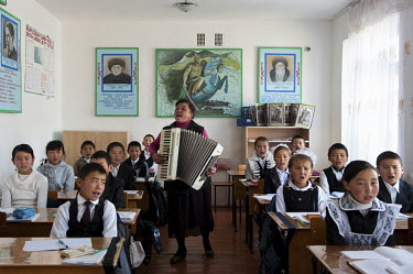 Students sing traditional Kyrgyz songs while their music teacher plays an accordion during a music class.