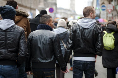 Three men hold hands as they march during the 'Big Equality Demonstration' held in the streets of Paris between the Place de la Bastille and the Place Saint Michel by supporters of a proposed law that...