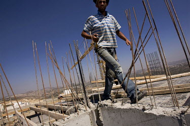 A Palestinian labourer walks over a reinforced concrete roof on a construction site in an Israeli settlement. Thousands of Palestinian construction workers, seeking work, cross from the West Bank into...