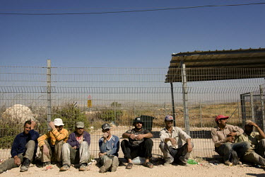 Palestinian labourers wait at a gate that leads into the West Bank, on the outskirts of the Israeli settlement where they work. Thousands of Palestinian construction workers, seeking work, cross from...