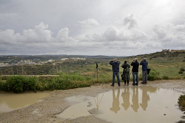 Volunteers look across a valley during an afternoon monitoring shift.Under EU leglislation, hunting or trapping birds in spring is illegal but the government of Malta, which joined the EU in 2004, all...