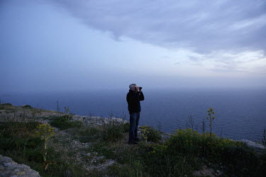 A volunteer with Spring Watch Malta monitors the horizon for migrating birds.Under EU leglislation, hunting or trapping birds in spring is illegal but the government of Malta, which joined the EU in 2...