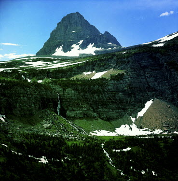 A rocky landscape with a snowy peak visible in the background in Glacier National Park, Montana.